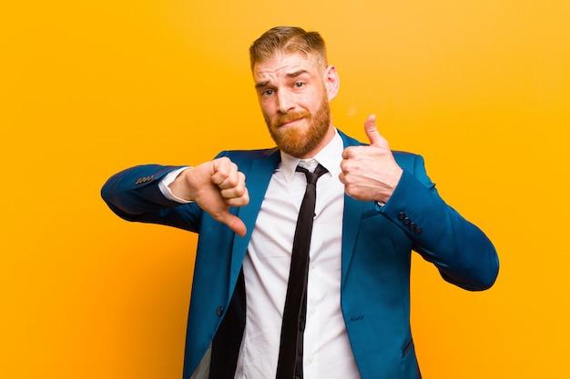 混乱、無知、不確かな感じの若い赤い頭の実業家、オレンジに対してさまざまなオプションや選択肢の善悪 Premium写真