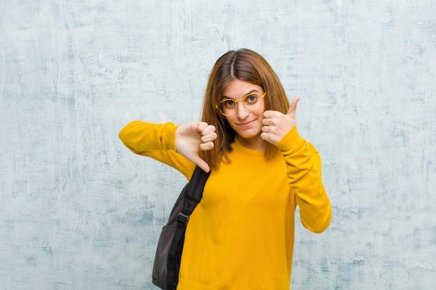 Молодая студентка чувствует себя смущенной, невежественной и неуверенной, взвешивая хорошее и плохое в различных вариантах или вариантах против гранжевой стены Premium Фотографии