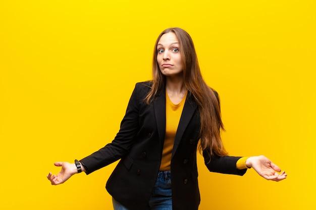 オレンジ色の背景に対して愚かなまたは愚かな表情で絶対に困惑して、無知で混乱し、見当がつかない感じの若いかなり実業家 Premium写真