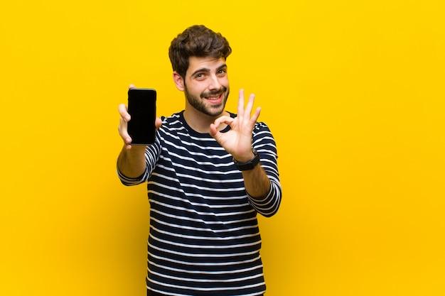 Молодой красивый мужчина против апельсина Premium Фотографии