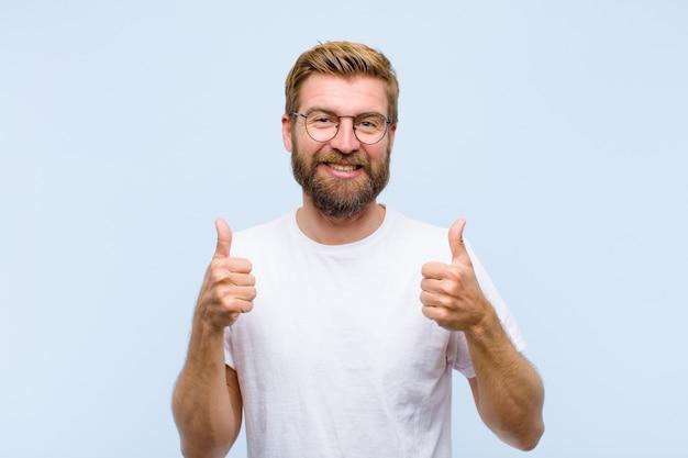Молодая блондинка взрослый мужчина широко улыбаясь счастливым, позитивным, уверенным и успешным, с большими пальцами руки вверх Premium Фотографии