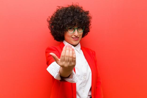 Молодая симпатичная афро женщина, чувствуя себя счастливой, успешной и уверенной в себе, сталкивается с вызовом и говорит: «приведи его! или приветствовать вас Premium Фотографии