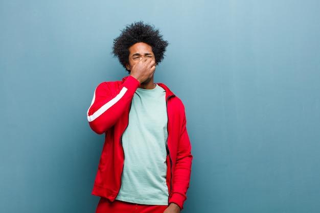 若い黒人スポーツ男はうんざりして、グランジの壁に悪臭と不快な悪臭の臭いを避けるために鼻を保持 Premium写真