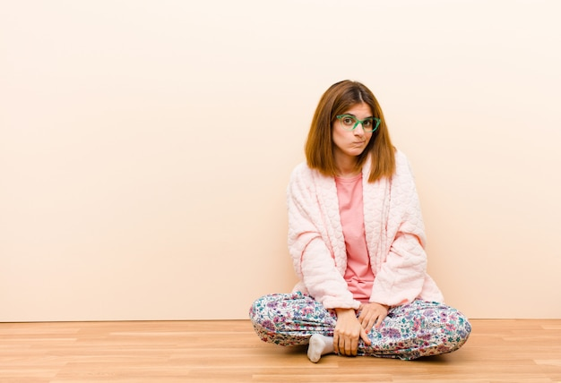 自宅で座っているパジャマを着た若い女性は混乱と疑わしい感じ Premium写真