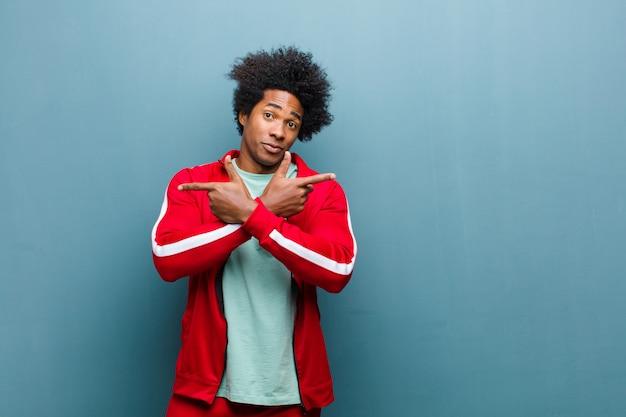 探している若い黒人スポーツ男困惑し、混乱し、不安定で、グランジの壁に対して疑いの反対の方向を指しています。 Premium写真