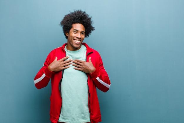Молодой черный спортивный человек выглядит счастливым, удивленным, гордым и взволнованным, указывая на себя против стены гранж Premium Фотографии