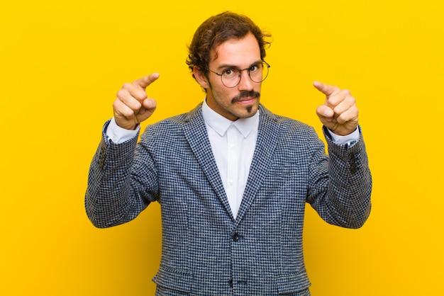 オレンジ色の壁に対してあなたの義務を行うように言って、指と怒りの両方の表現でカメラを前方に指している若いハンサムな男 Premium写真