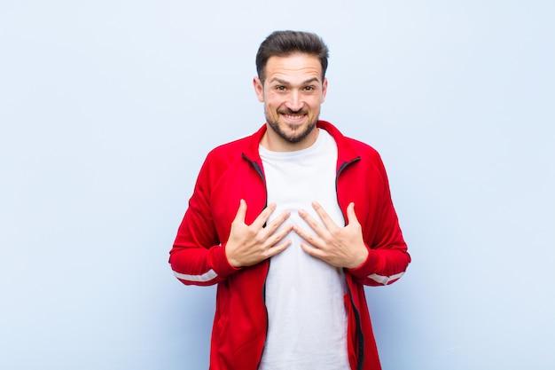 若いハンサムなスポーツ男またはモニター、幸せ、驚き、誇りと興奮を探して Premium写真