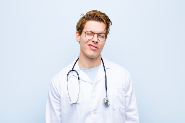 Молодой рыжий доктор смотрит счастливым и дружелюбным, улыбается и подмигивает глазу Premium Фотографии