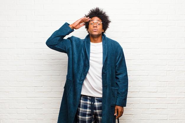 Молодой черный человек в пижаме с платьем приветствует камеру с военным салютом в акте чести и патриотизма, показывая уважение Premium Фотографии