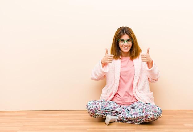 Молодая женщина в пижаме, сидя дома, широко улыбаясь, счастливые, позитивные, уверенные и успешные, с большими пальцами руки вверх Premium Фотографии