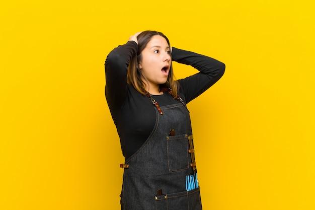 Женщина-парикмахер с открытым ртом, выглядит испуганной и шокированной из-за ужасной ошибки, поднимая руки к голове на оранжевом фоне Premium Фотографии