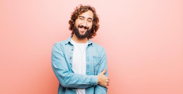 Молодой бородатый сумасшедший смеется застенчиво и весело, с дружелюбным и позитивным, но неуверенным отношением Premium Фотографии