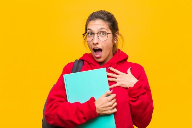 胸に手を当てて口を開け、ショックを受け、驚いて、驚いた若い可愛い学生は、誰と言ったの? Premium写真
