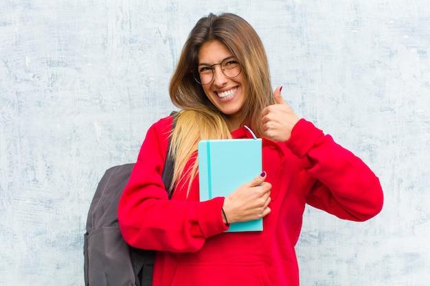 Молодой симпатичный студент, широко улыбаясь, выглядит счастливым, позитивным, уверенным и успешным, оба больших пальца вверх Premium Фотографии