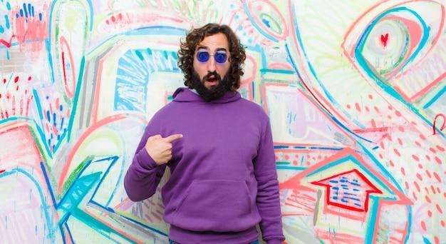 若者は、混乱し、困惑し、不安を感じて、自分自身に疑問を抱き、誰に尋ねているのかを尋ねて、狂気の男を生やしましたか?落書きの壁に対して Premium写真