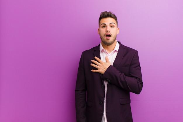 ショックを受けて驚いた、笑みを浮かべて、手をつないで、喜んでいる、または感謝を示しているヒスパニック青年 Premium写真