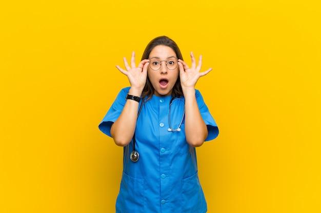 黄色に対して隔離された驚いた、信じられない表情でメガネを保持している、ショックを受け、驚き、驚きを感じる Premium写真