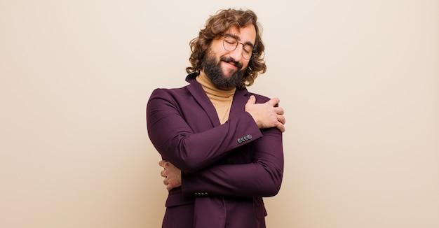 Молодой бородатый сумасшедший чувствует себя влюбленным, улыбается, обнимает и обнимает себя, остается одиноким, эгоистичным и эгоцентричным по отношению к плоскому цвету Premium Фотографии
