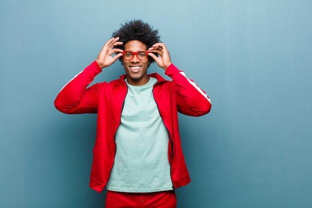 グランジの壁に対して驚いた、信じられない表情でメガネを保持しているショックを受けて、驚いて、驚いた若い黒人スポーツ男 Premium写真