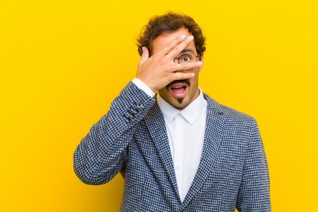 ショックを受けた、怖がっている、または恐怖を探している若いハンサムな男、手で顔を覆って、オレンジに対して指の間を覗く Premium写真