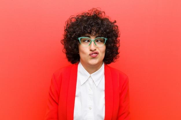愚かな寄り目式で間抜けで面白い探して、冗談と浮気の若いかなりアフロ女性 Premium写真