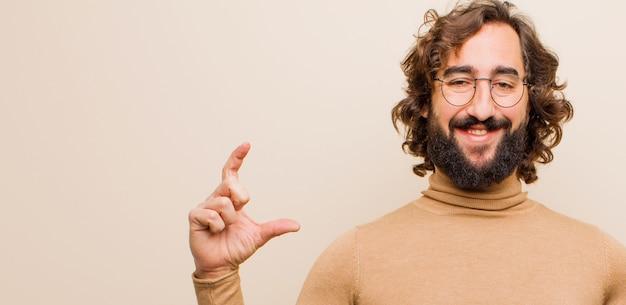 Молодой бородатый сумасшедший мужчина, обрамляющий или обрисовывающий в общих чертах собственную улыбку обеими руками, выглядящий позитивным и счастливым, концепция здоровья на фоне плоской цветной стены Premium Фотографии