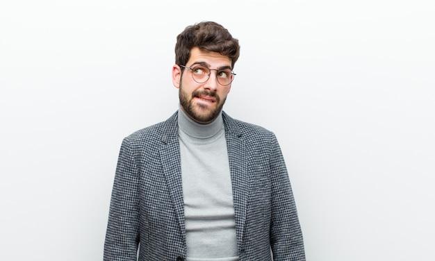 Молодой менеджер мужчина выглядит озадаченным и растерянным, кусая губу нервным жестом, не зная ответа на проблему у белой стены Premium Фотографии
