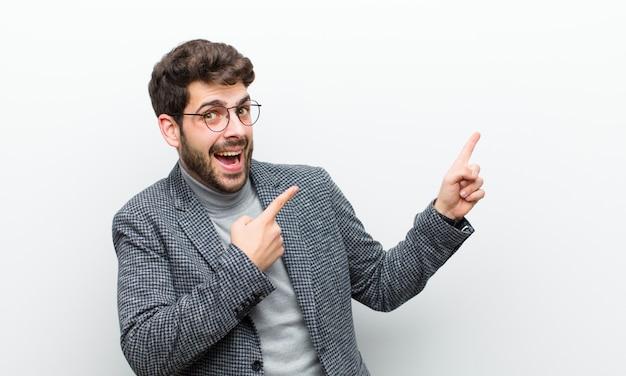 喜びと驚きを感じて、ショックを受けた表情で笑顔と白い壁に対して側を指している若いマネージャー男 Premium写真
