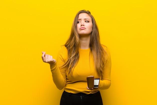 オレンジ色の壁に対して若いきれいな女性お金の概念 Premium写真
