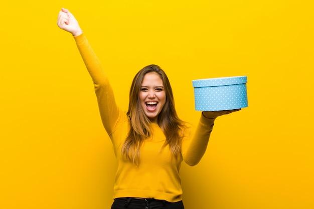 オレンジ色の壁にギフトボックスを持つ若いきれいな女性 Premium写真
