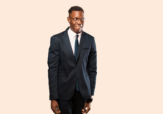 Афро-американский бизнесмен, выглядящий взволнованным, подчеркнутым, взволнованным и напуганным, паникующим и стискивающим зубы на бежевой стене Premium Фотографии