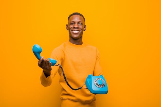 ビンテージ電話でオレンジ色の壁に若いアフリカ系アメリカ人の黒人男性 Premium写真
