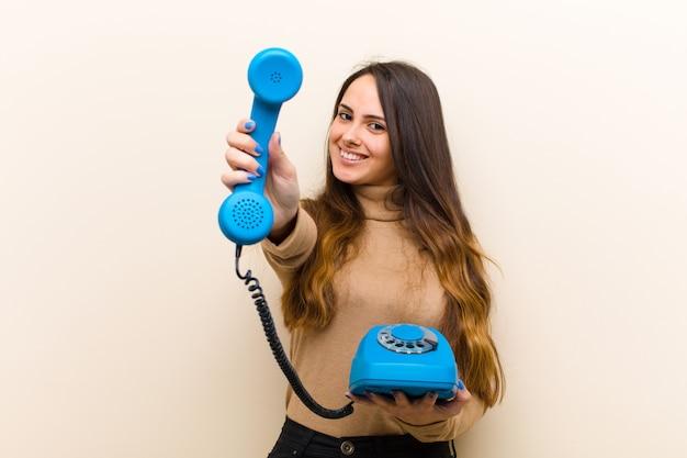 Молодая милая женщина с голубым винтажным телефоном Premium Фотографии