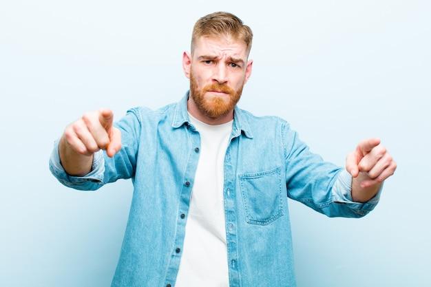 Молодой рыжий мужчина, указывая пальцем на камеру и сердитое выражение лица, говоря вам, чтобы выполнить свой долг Premium Фотографии