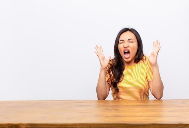 Молодая латинская красотка яростно кричит, чувствуя напряжение и раздражение, поднимая руки вверх, говоря, почему я за стеной Premium Фотографии
