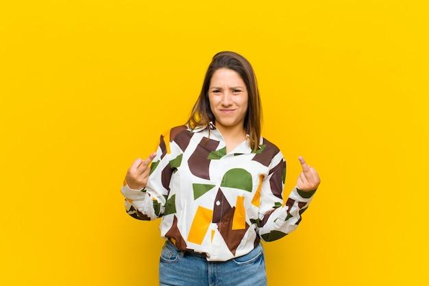Латиноамериканская женщина чувствует себя провокационно, агрессивно и непристойно, переворачивая средний палец, с бунтарским отношением к желтой стене Premium Фотографии