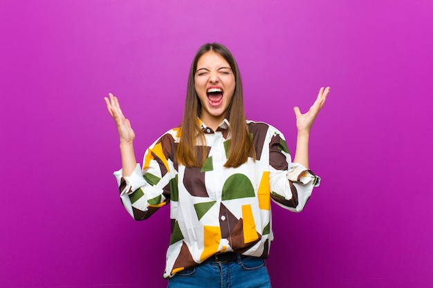 Молодая симпатичная женщина яростно кричит, чувствуя стресс и раздражение с поднятыми вверх руками, говоря, почему я за фиолетовой стеной Premium Фотографии
