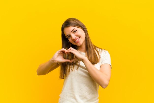 Молодая красивая женщина улыбается и чувствует себя счастливой, милой, романтичной и влюбленной, делая форму сердца обеими руками над оранжевой стеной Premium Фотографии