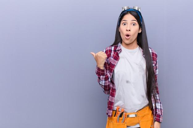 Молодая женщина выглядит удивленной в неверии, указывая на объект на стороне и говоря вау, невероятно Premium Фотографии