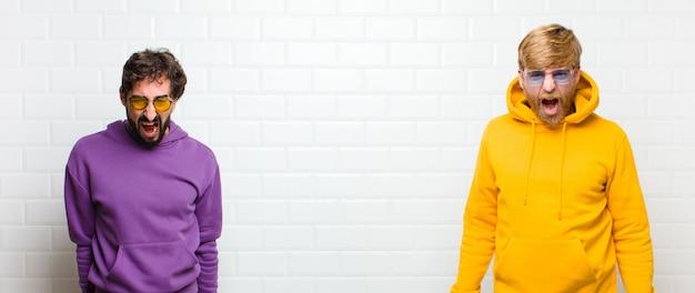 Молодые спокойные мужчины, агрессивно кричащие, выглядящие очень злыми, разочарованными, возмущенными или раздраженными, кричащими не над белой плиткой стены Premium Фотографии
