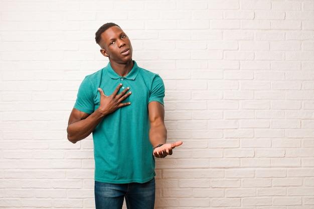 Молодой афроамериканец темнокожий мужчина, чувствуя себя счастливым и влюбленным, улыбаясь одной рукой рядом с сердцем, а другой растянулся вперед над кирпичной стеной Premium Фотографии