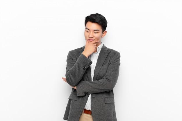 若いアジア人のあごに手で幸せ、自信を持って表情に笑みを浮かべて、不思議と色の壁を越えて側に見て Premium写真