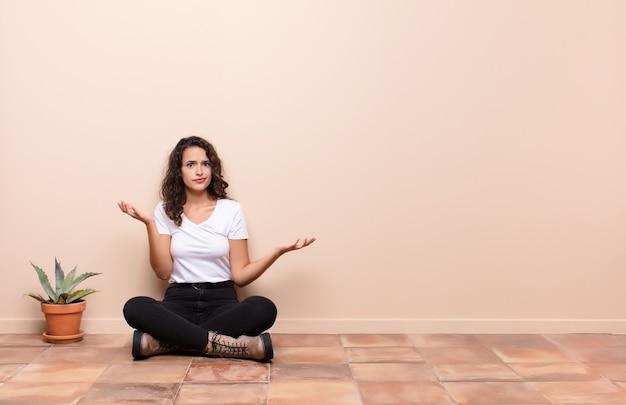 Молодая симпатичная женщина пожимает плечами с тупым, сумасшедшим, растерянным, озадаченным выражением, чувствуя себя раздраженным и невежественным, сидя на полу террасы Premium Фотографии
