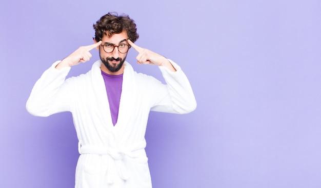 Молодой бородатый мужчина носит халат с серьезным и сосредоточенным взглядом, мозговой штурм и думает о сложной проблеме Premium Фотографии