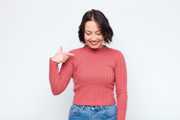 Молодая красивая женщина весело и небрежно улыбаясь, глядя вниз и указывая на грудь на белой стене Premium Фотографии