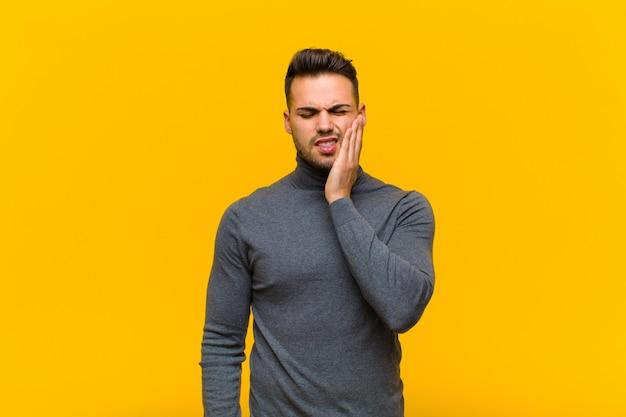 頬を保持し、痛みを伴う歯痛に苦しんで、病気、悲惨、不幸を感じて、オレンジ色の壁に対して歯科医を探しているヒスパニック青年 Premium写真