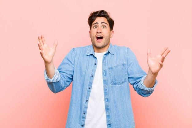 Молодой красавец, чувствуя себя счастливым, удивленным, удачливым и удивленным, празднуя победу обеими руками в воздухе у розовой стены Premium Фотографии