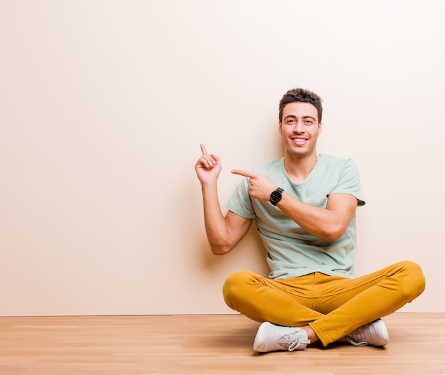 幸せな笑みを浮かべて、床に座ってコピースペースでオブジェクトを示す両方の手で側と上を指している若いアラビア人 Premium写真