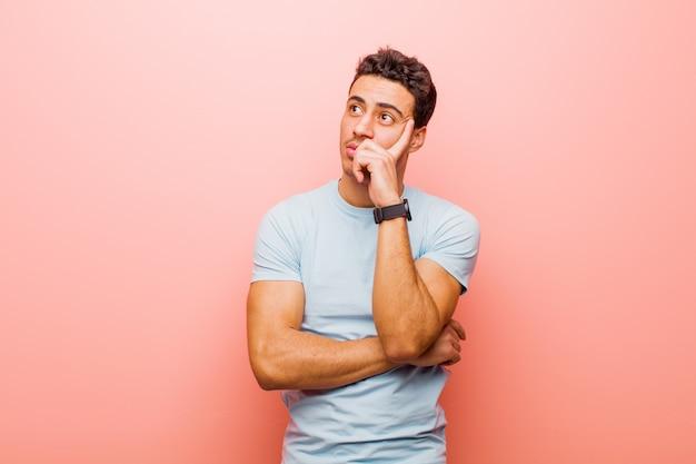 集中力のある表情で、疑わしい表情で疑問に思って、見上げるとピンクの壁の側にいる若いアラビア人 Premium写真